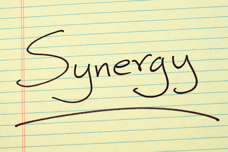 The word Synergy underlined on a yellow legal pad