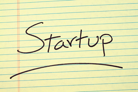 The word Startup underlined on a yellow legal pad