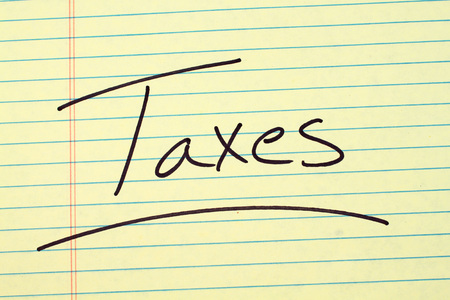 governement: The word Taxes underlined on a yellow legal pad