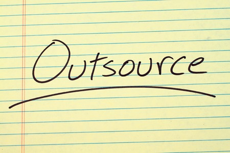 The word Outsource underlined on a yellow legal pad