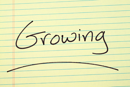 The word Growing underlined on a yellow legal pad Stock fotó