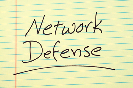 The word Network Defense underlined on a yellow legal pad Stock Photo