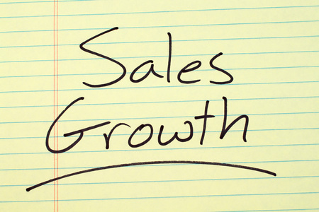 The word Sales Growth underlined on a yellow legal pad