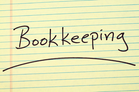 The word Bookkeeping underlined on a yellow legal pad