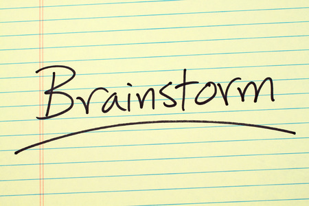 The word Brainstorm underlined on a yellow legal pad