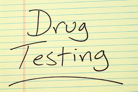 The word Drug Testing underlined on a yellow legal pad Stock fotó