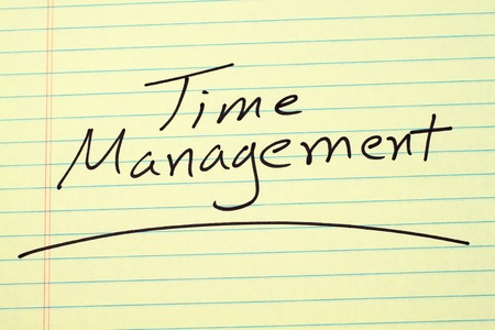 The word Time Management underlined on a yellow legal pad