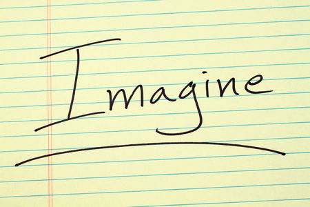 The word Imagine underlined on a yellow legal pad