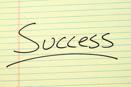 The word Success underlined on a yellow legal pad