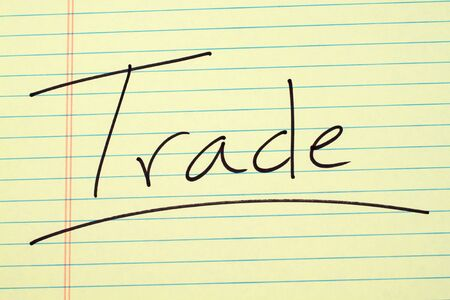 The word Trade underlined on a yellow legal pad