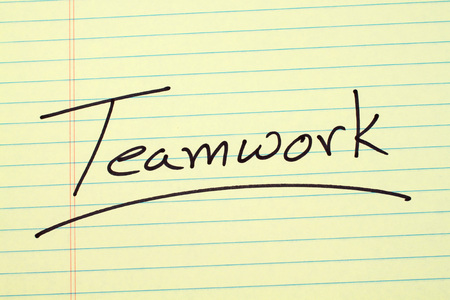 The word Teamwork underlined on a yellow legal pad