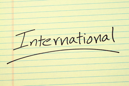 The word International underlined on a yellow legal pad