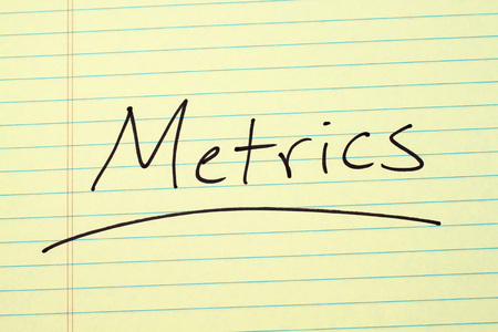 The word Metrics underlined on a yellow legal pad Stock fotó