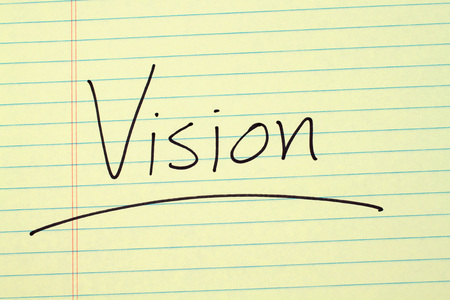 The word Vision underlined on a yellow legal pad