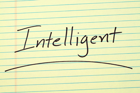 The word Intelligent underlined on a yellow legal pad