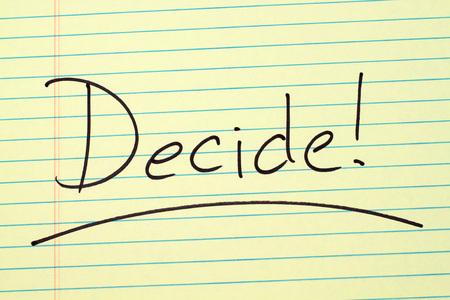 The word Decide! underlined on a yellow legal pad