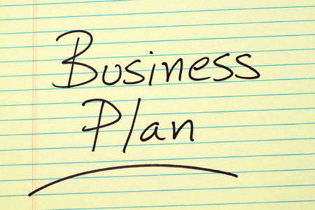 The word Business Plan underlined on a yellow legal pad Stock fotó