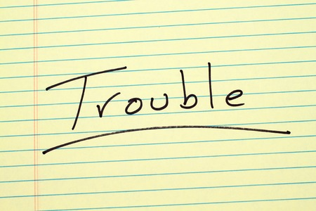 The word Trouble underlined on a yellow legal pad 版權商用圖片