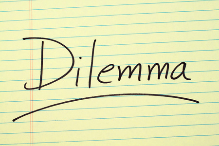 The word Dilemma underlined on a yellow legal pad