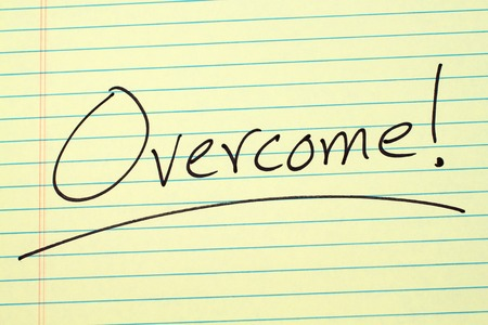 The word Overcome! underlined on a yellow legal pad
