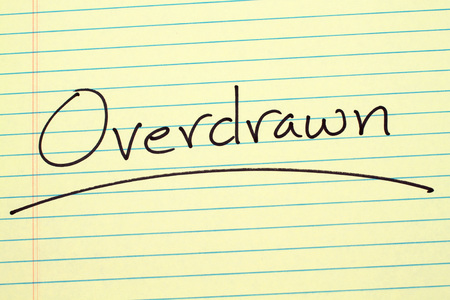 The word Overdrawn underlined on a yellow legal pad
