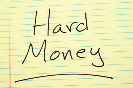 The word Hard Money underlined on a yellow legal pad