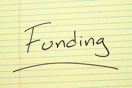 The word Funding underlined on a yellow legal pad