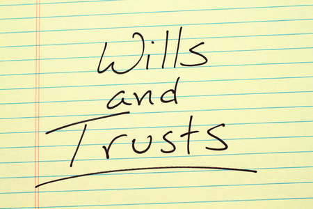 The word Wills and Trusts underlined on a yellow legal pad