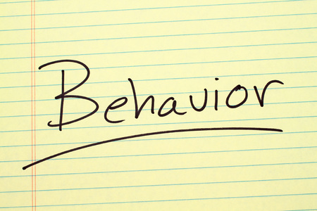 The word Behavior underlined on a yellow legal pad