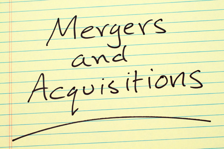 The word Mergers And Acquisitions underlined on a yellow legal pad
