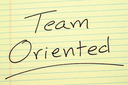 The word Team Oriented underlined on a yellow legal pad