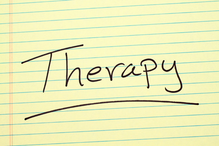 The word Therapy underlined on a yellow legal pad