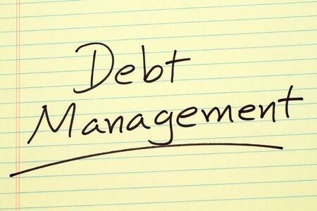 The word Debt Management underlined on a yellow legal pad