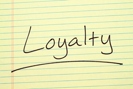 The word Loyalty underlined on a yellow legal pad