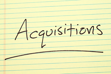 The word Acquisitions underlined on a yellow legal pad