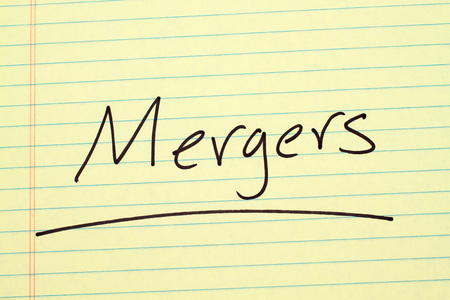 The word Mergers underlined on a yellow legal pad