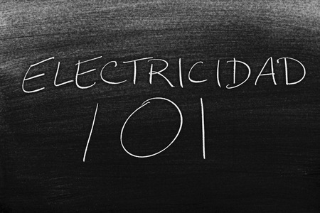 The words Electricidad 101 on a blackboard in chalk.  Translation: Electricity 101