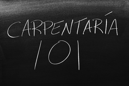 The words Carpintería 101 on a blackboard in chalk.  Translation: Carpentry 101