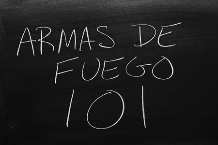 The words Armas De Fuego 101 on a blackboard in chalk.  Translation: Guns 101
