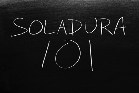 The words Soldadura 101 on a blackboard in chalk.  Translation: Welding 101