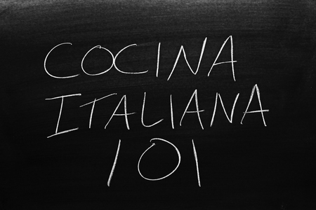 The words Cocina Italiana 101 on a blackboard in chalk.  Translation: Italian Cooking 101 Stock Photo