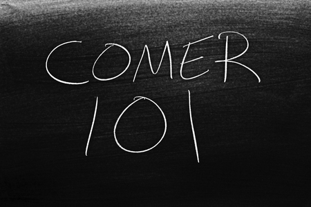 The words Comer 101 on a blackboard in chalk.  Translation: Eating 101
