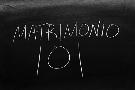 The words Matrimonio 101 on a blackboard in chalk.  Translation: Marriage 101