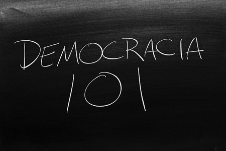 The words Democracia 101 on a blackboard in chalk.  Translation: Democracy 101