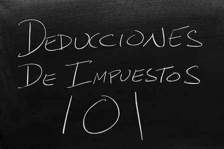 The words Deducciones De Impuestos 101 on a blackboard in chalk.  Translation: Tax Deductions 101