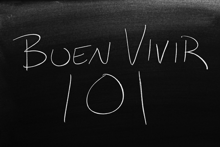 The words Buen Vivir 101 on a blackboard in chalk.  Translation: Living Well 101 Stock Photo