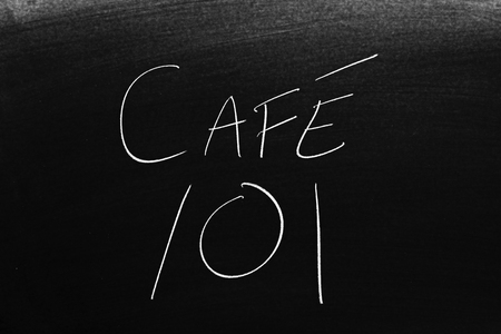 The words Café 101 on a blackboard in chalk.  Translation: Coffee 101 Stock Photo