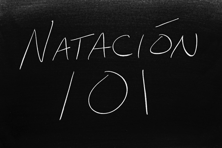 The words Natación 101 on a blackboard in chalk.  Translation: Swimming 101