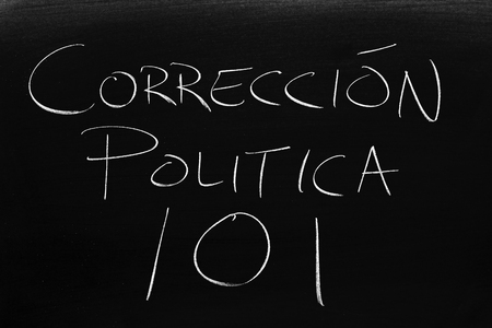 The words Corrección Política 101 on a blackboard in chalk.  Translation: Political Correctness 101 Stock Photo