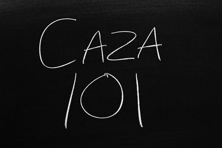 The words Caza 101 on a blackboard in chalk.  Translation: Hunting 101